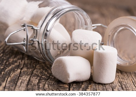 Marshmallows spilling from a storage jar, over wood background.