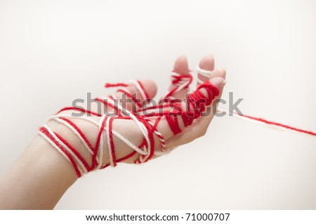 Martenitsa is a small piece of adornment, made of white and red threads. It symbolizes spring and the wish for good health. Worn on 1st March in Bulgaria. This holiday is called Baba Marta. - stock photo