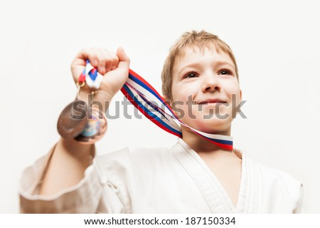Martial art sport success and win concept - smiling karate champion child boy hand holding first place victory gold medal award - stock photo