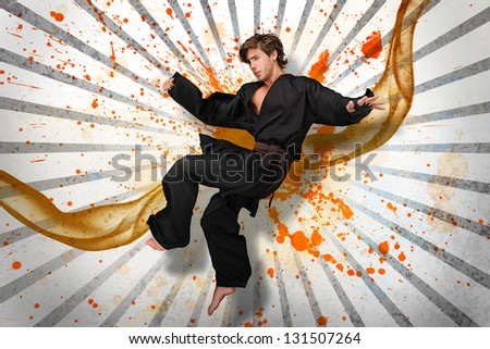 Martial arts expert mid air on linear pattern with orange paint splashes and vapour - stock photo