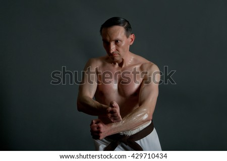 Martial arts fighter stands in defense position. Artistic studio lighting.  - stock photo