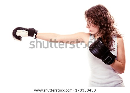 Martial arts or emancipation idea concept. Sport boxer woman in black gloves. Fitness girl training kick boxing showing her power domination. Isolated on white background. - stock photo