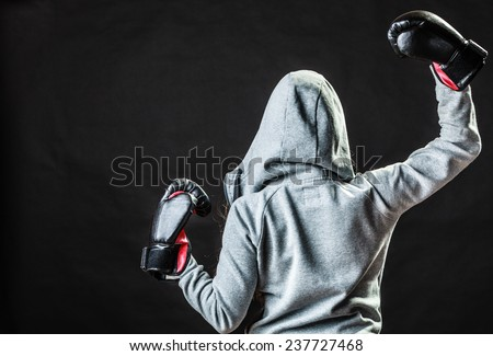 Martial arts or self defence concept. Sport boxer woman in gloves. Fitness girl training kick boxing back view on black background - stock photo