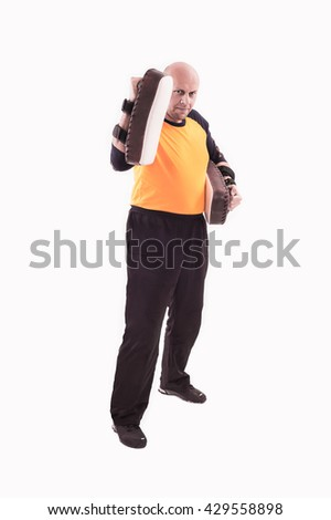 Martial arts trainer holding kick-shield