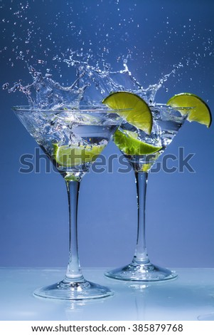 Martini alcohol cocktail with splash and green lime - stock photo
