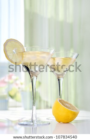 Martini alcohol cocktail with yellow lemon on white table - stock photo