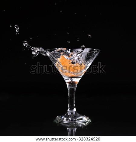 martini cocktail splashing into glass on black background - stock photo