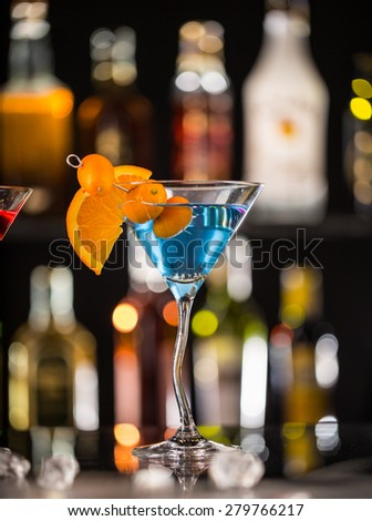 Martini drink served on glass table with colored dark background and ice cubes
