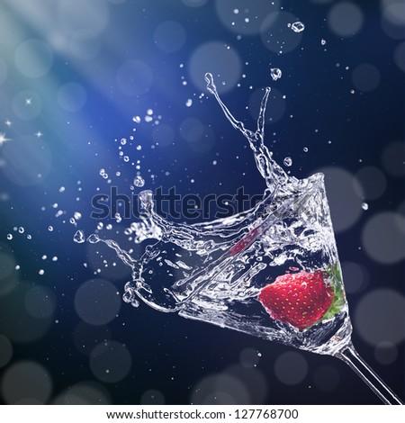 Martini drink splashing out of glass - stock photo