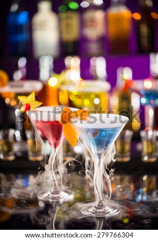 Martini drinks with dry ice smoke effect, served on bar counter with blur bottles on background