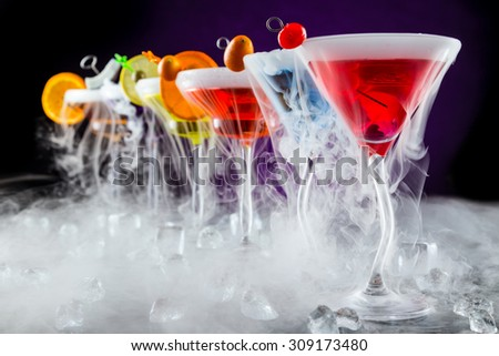 Martini drinks with dry ice smoke effect, served on bar counter with dark colored background - stock photo