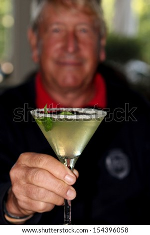 Martini glass held by senior male - stock photo