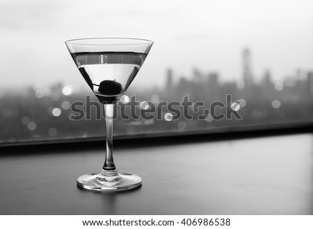 Martini glass in a restaurant setting with city views.  - stock photo