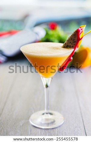 martini glass on a wooden table with fresh delicious cocktail of passion fruit - stock photo