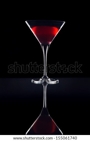 martini glass with liquid is poured on a black background is. - stock photo