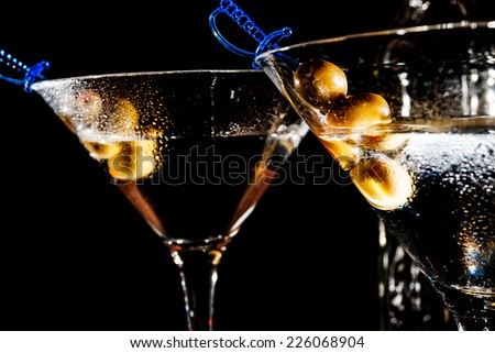 Martini glass with olive on black background - stock photo