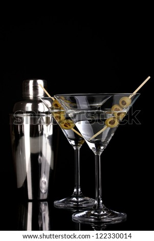 Martini glass with olives and shaker isolated on black - stock photo