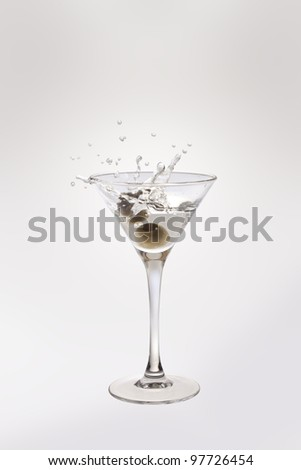 Martini glass with olives and splash - stock photo