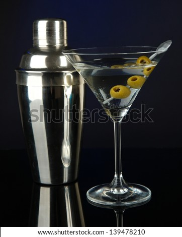 Martini glass with olives on dark blue background - stock photo