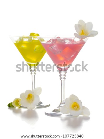 martini glasses of cocktails with ice and flowers isolated on white - stock photo