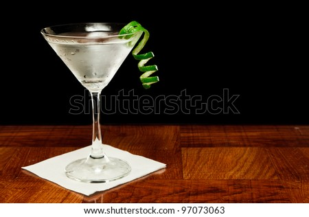 martini on a bar top garnished with a fresh lime twist - stock photo