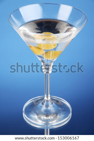 Martini with green olives on blue background