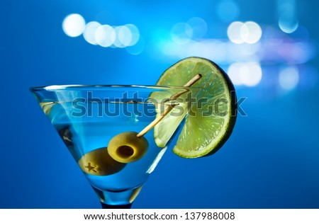 martini with lime and green olives on a blue background. - stock photo