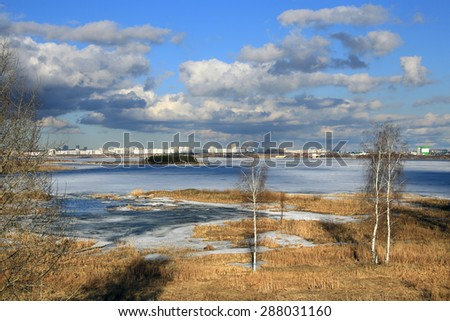 marvelous spring landscape view of the broad river and the city on the horizon on a cloudy day - stock photo