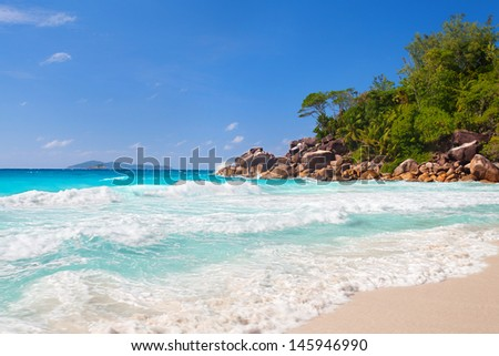 marvelous waves at the White sand beach on seychelles, turquoise water and blue sky - stock photo