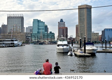 MARYLAND, USA - JUNE 4, 2016: A father and his daughter sitting on the ledge next to the Baltimore harbor enjoying their day together in the park.