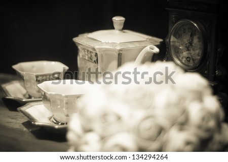 Marzipan flower boquet with antique tea cups on the table, old brown black and white