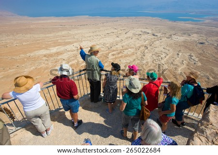 MASADA, ISRAEL - OCT 14, 2014: A guide gifts an explanation about Masada to tourists  - stock photo