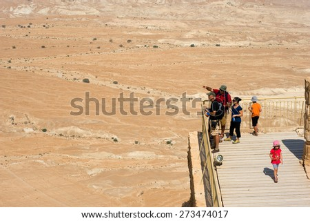 MASADA, ISRAEL - OCT 14, 2014: Tourists are enjoying the view from the lower terrace of the palace of king Herod on the rock Masada in Israel