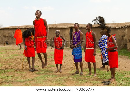 MASAI MARA, KENYA - AUGUST 24: A group of kenyan of Masai tribe performs traditional dancing jump to welcome their visitors on August 24, 2011 in a local village near Masai Mara National Park, Kenya. - stock photo