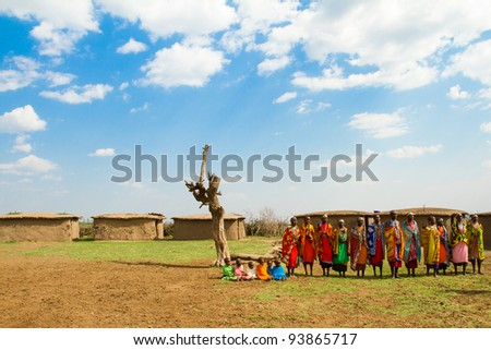 MASAI MARA, KENYA - AUGUST 24: A group of kenyan women of Masai tribe sings a traditional song to welcome their visitors on August 24, 2011 in a local village near Masai Mara National Park, Kenya. - stock photo