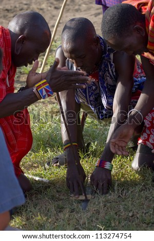 MASAI MARA, KENYA - JANUARY 4: Maasai warriors showing how they make fire in a traditional way to guests visiting their village taken on January 4, 2012  in Masai Mara, Kenya. - stock photo
