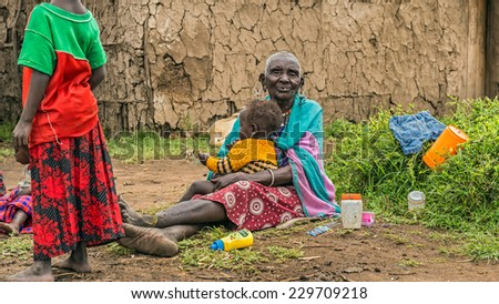 MASAI MARA, KENYA - OCTOBER 17, 2014: Old African woman from Masai tribe holding a baby in her village. The Maasai are a Nilotic ethnic group living in southern Kenya and northern Tanzania - stock photo