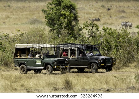 MASAI MARA, KEYNA-AUGUST 20: Tourist enjoying game drive on safari Jeep in Masai Mara National Reserve on August 20, 2016 at Masai Mara, Kenya, Africa