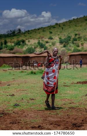 MASAI MARA - OCTOBER 02 : Young male playing in masai village on October 02 , 2013 in Masai Mara,Kenya - stock photo