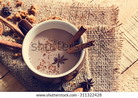 masala chai chocolate with spices and star Anise, cinnamon stick, peppercorns, on sack and wooden background, vintage color tone - stock photo
