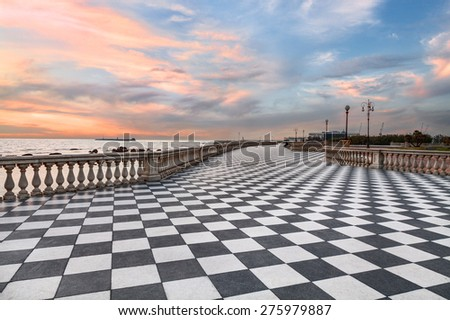 Mascagni Terrace, promenade of Livorno, Tuscany, Italy, picturesque seashore at sunset with black and white checkered pavement and columned bannister