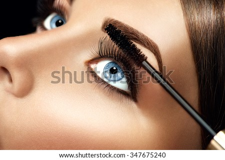 Mascara applying closeup, long lashes. Mascara brush. Eyelashes extensions. Make-up for blue eyes. Eye make up apply - stock photo