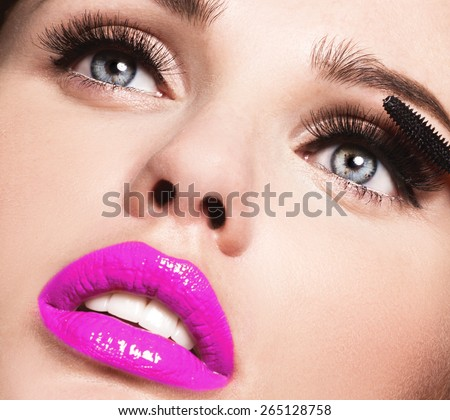 Mascara Applying. Long Lashes closeup. Mascara Brush. Eyelashes extensions. Makeup for Blue Eyes. Eye Make up Apply,pink lips - stock photo