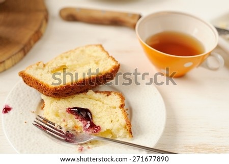 Mascarpone cake slice, cup of tea in orange teacup, table knife, blueberry jam on white bright background - stock photo