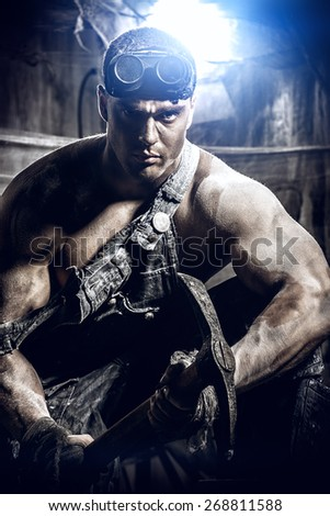 Masculine dirty coal miner with a pickaxe over dark grunge background. Mining industry. Strength. Bodybuilding. - stock photo