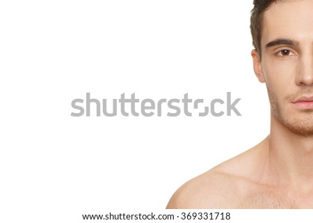 Masculine perfection. Half face cropped studio shot of a young handsome man copyspace on the side - stock photo