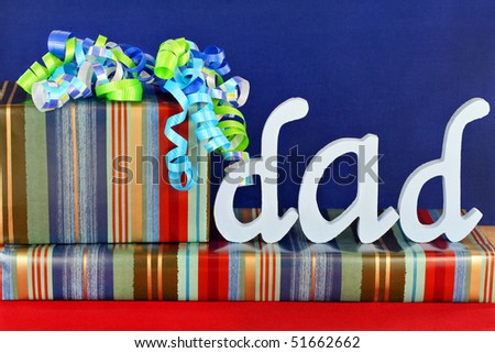 Masculine wrapped gifts with ribbons and the word Dad on top.  Ideal for dad's birthday or father's day. - stock photo