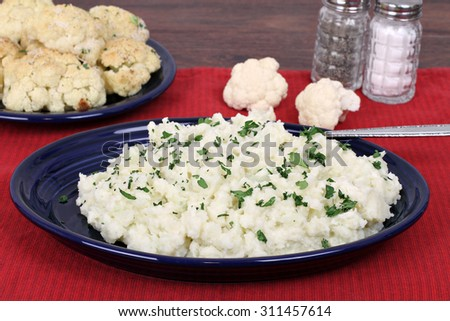 Mashed cauliflower,  a healthy substitite for potatoes, on a plate with roasted cauliflower in the background.