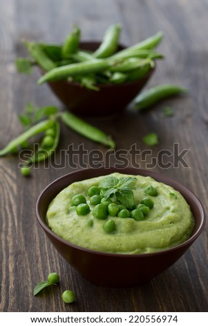 Mashed green peas and potatoes in a bowl on a wooden table - stock photo