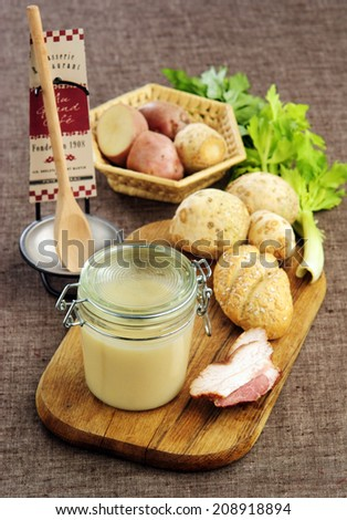 Mashed potato soup with ham in the pot on a wooden board against dark background - stock photo